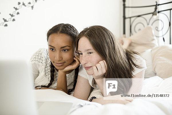 Zwei Teenager-Mädchen liegen auf dem Bett und schauen auf den Laptop.