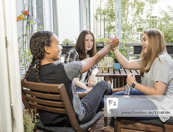 Drei fröhliche Teenager-Mädchen sitzen auf einem Balkon