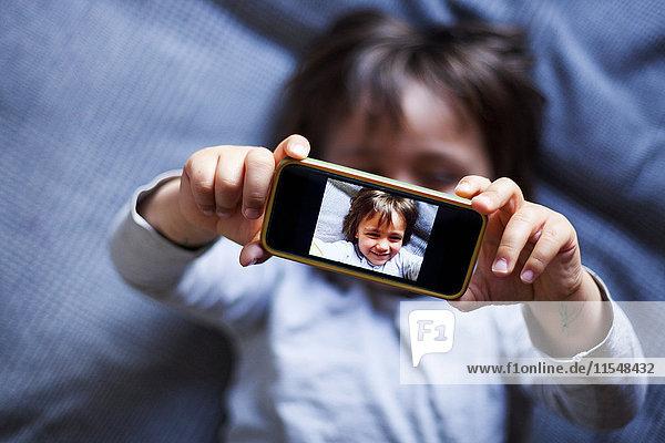 Kleiner Junge nimmt Selfie mit Smartphone