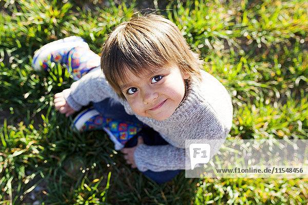 Portrait of smiling boy sitting in meadow