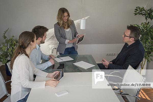 Frau leitet eine Präsentation mit digitalem Tablett im Konferenzraum