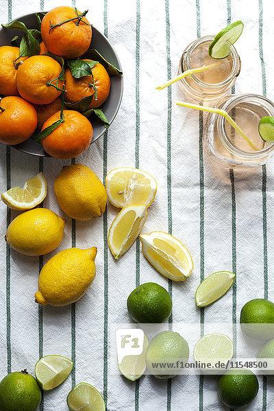 Zwei Gläser Limonade und verschiedene Zitrusfrüchte