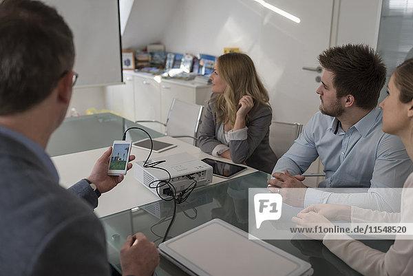 Vier Kollegen bei einer Präsentation mit Smartphone und Projektor im Konferenzraum