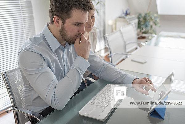 Zwei Kollegen teilen sich ein digitales Tablett im Büro
