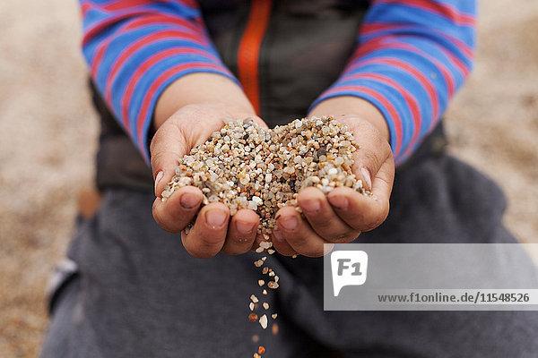 Hände des kleinen Jungen mit Sand  Nahaufnahme