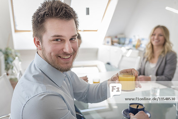 Smiling man holding glass of orange juice in office