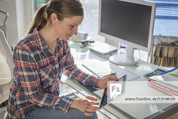 Junge Frau am Schreibtisch im Büro mit Blick auf das digitale Tablett