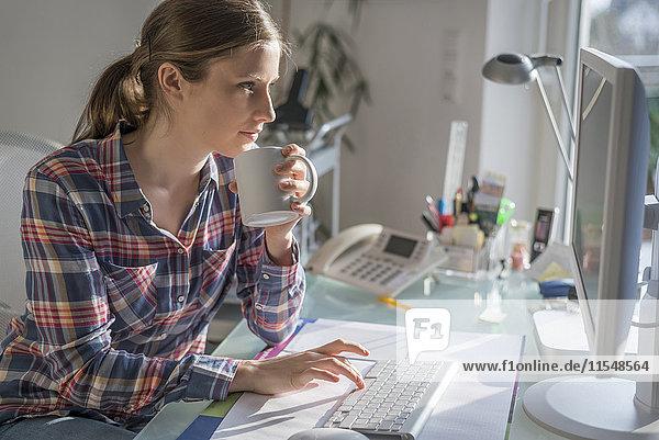 Junge Frau am Schreibtisch im Büro mit einer Tasse Kaffee