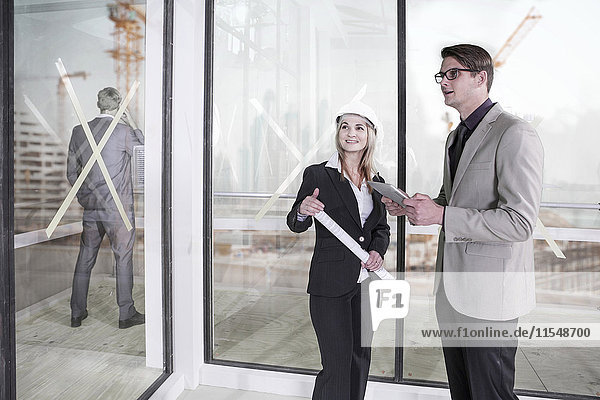 Businessmen and woman with hard hat talking on construction site