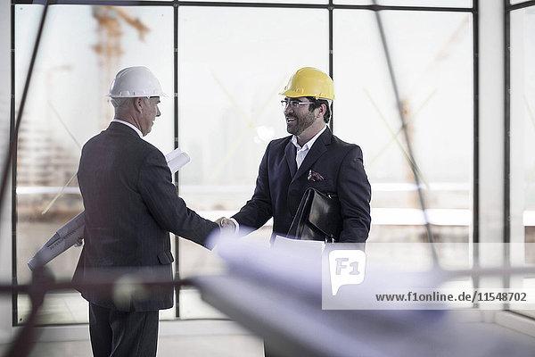 Zwei Geschäftsleute mit Schutzhelmen  die auf der Baustelle die Hand schütteln.