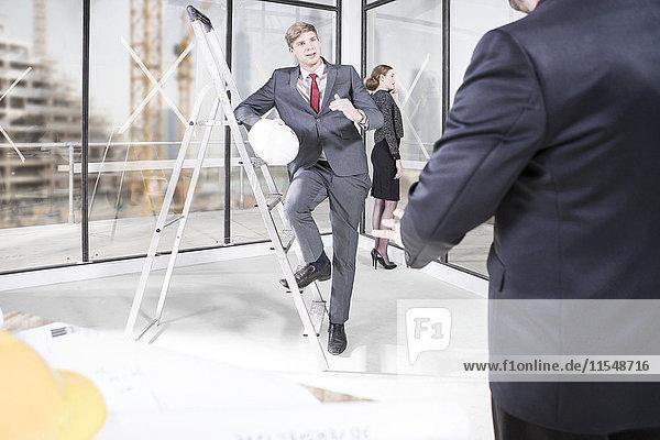 Geschäftsmann mit Schutzhelm im Büro im Aufbau