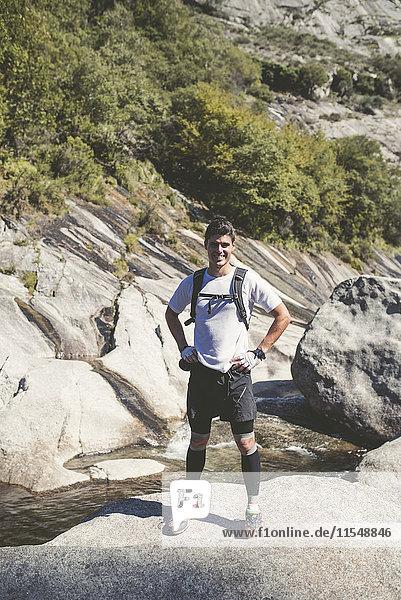 Spanien  A Capela  Porträt eines lächelnden Langläufers auf einem Felsen stehend