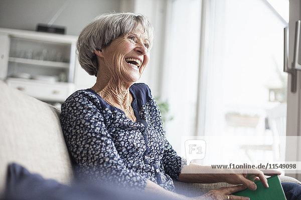 Porträt einer glücklichen Seniorin,  die zu Hause auf der Couch sitzt.