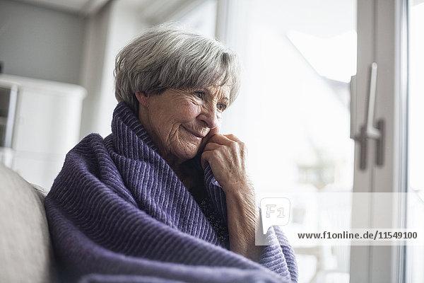 Porträt einer nachdenklichen Seniorin  die zu Hause auf der Couch sitzt.