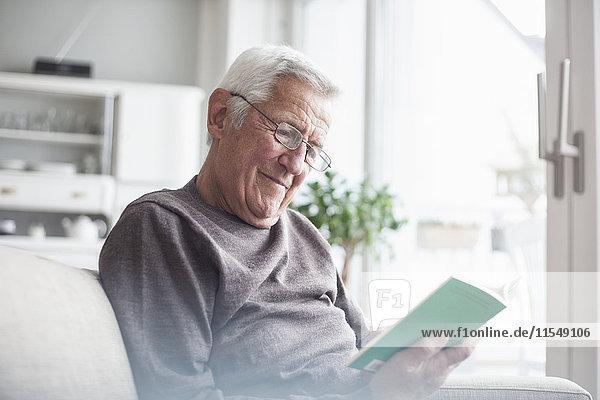 Porträt eines älteren Mannes  der zu Hause auf der Couch sitzt und ein Buch liest.