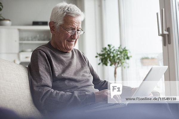 Porträt eines älteren Mannes  der zu Hause auf der Couch sitzt und einen Laptop benutzt.