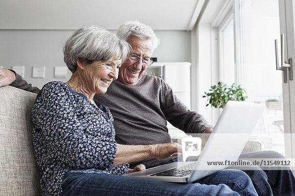 Glückliches Seniorenpaar sitzt auf der Couch im Wohnzimmer mit Laptop