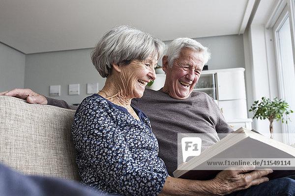 Lachendes Seniorenpaar sitzt auf der Couch im Wohnzimmer und schaut sich ein Fotoalbum an.