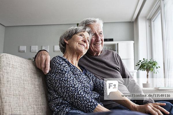Fröhliches Seniorenpaar sitzt zusammen auf der Couch im Wohnzimmer