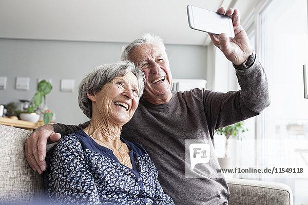Lachendes älteres Paar,  das auf der Couch im Wohnzimmer sitzt und Selfie mit Smartphone nimmt