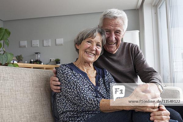 Glückliches älteres Paar,  das auf der Couch im Wohnzimmer sitzt und Händchen hält.
