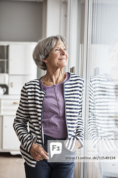Porträt einer selbstbewussten Seniorin mit Blick durchs Fenster