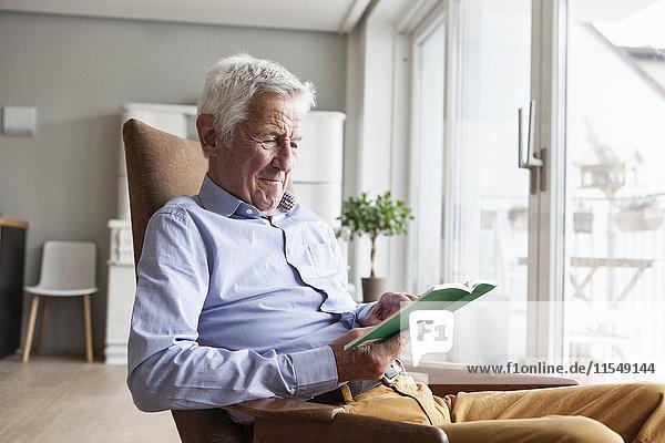 Porträt eines älteren Mannes  der zu Hause auf einem Sessel sitzt und ein Buch liest.