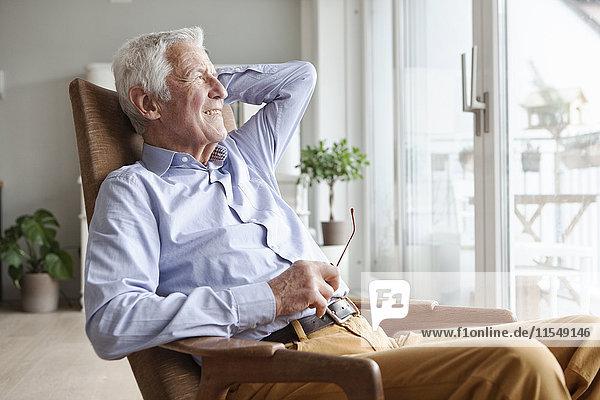 Porträt eines älteren Mannes  der sich zu Hause auf dem Sessel entspannt