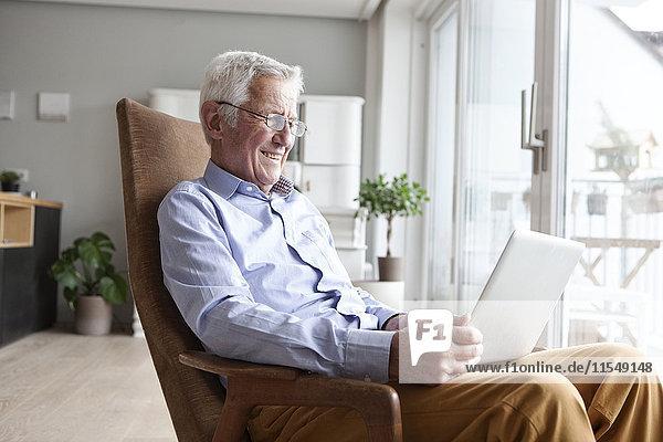 Porträt eines älteren Mannes  der zu Hause auf einem Sessel sitzt und einen Laptop benutzt.