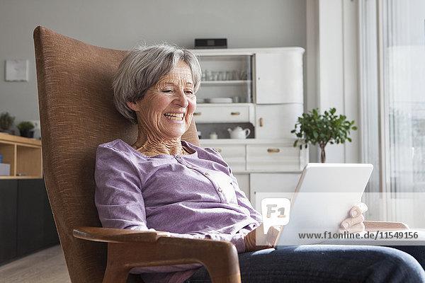 Porträt einer älteren Frau  die zu Hause auf einem Sessel sitzt und ein digitales Tablett benutzt.