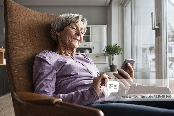 Porträt einer älteren Frau  die zu Hause auf einem Sessel sitzt und ein Smartphone benutzt.