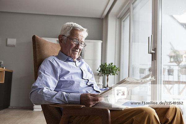 Porträt eines älteren Mannes  der zu Hause auf einem Sessel sitzt und Zeitung liest.