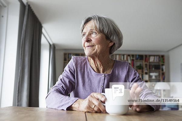 Porträt einer älteren Frau am Tisch mit einer Tasse Kaffee  die durchs Fenster schaut.