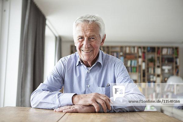 Porträt eines selbstbewussten älteren Mannes  der am Tisch im Wohnzimmer sitzt.