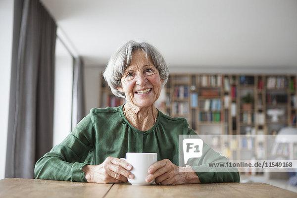 Porträt einer lächelnden Seniorin am Tisch mit einer Tasse Kaffee