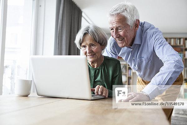 Senior Paar mit Laptop zu Hause