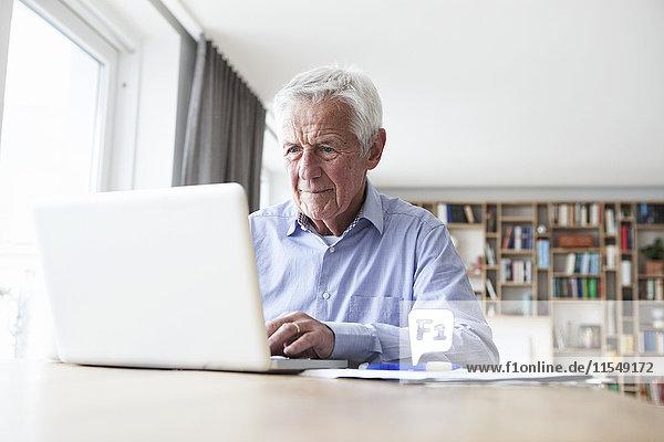 Porträt eines älteren Mannes am Tisch mit Laptop