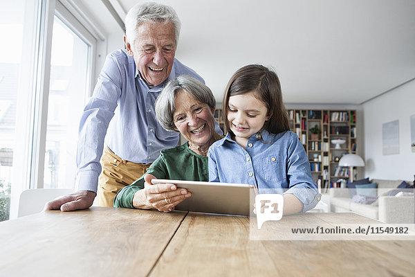Großeltern und ihre Enkelin mit digitalem Tablett zu Hause