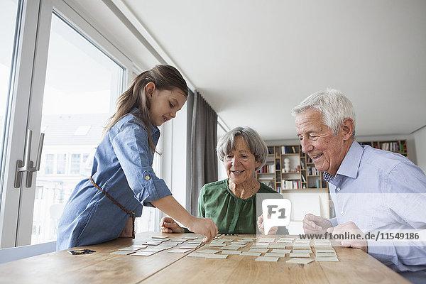 Kleines Mädchen  das mit seinen Großeltern zu Hause Erinnerungen spielt.