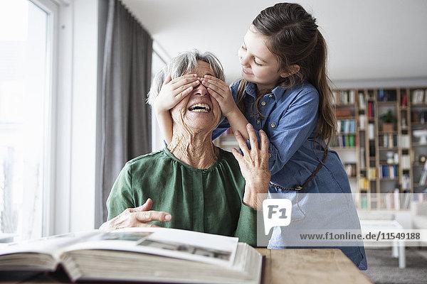 Kleines Mädchen  das die Augen seiner Großmutter mit den Händen bedeckt.
