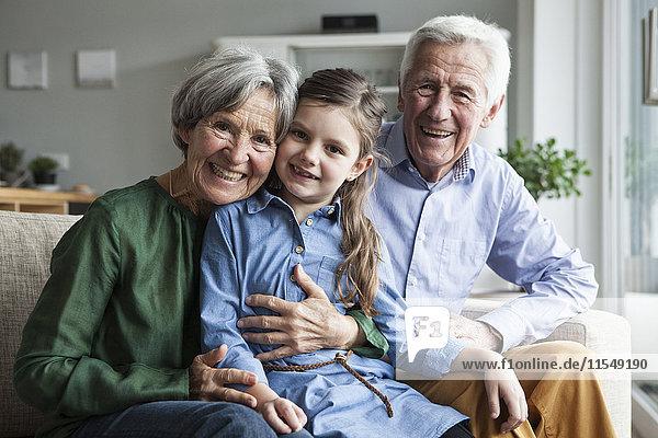 Familienportrait der Großeltern und ihrer Enkelin zu Hause
