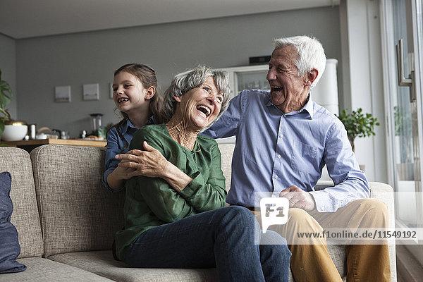 Kleines Mädchen und ihre Großeltern amüsieren sich zu Hause