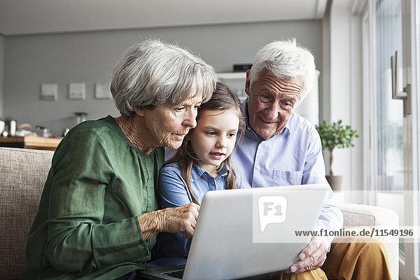 Großeltern und ihre Enkelin sitzen zusammen auf der Couch und schauen auf ein digitales Tablett.