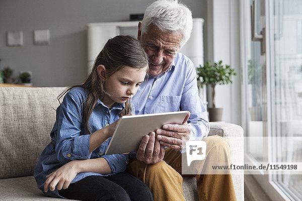 Großvater und seine Enkelin sitzen zusammen auf der Couch mit Hilfe eines digitalen Tabletts.