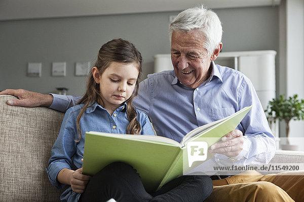 Großvater und seine Enkelin sitzen zusammen auf der Couch mit einem Buch.