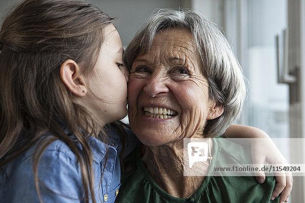Kleines Mädchen  das seine Großmutter küsst.