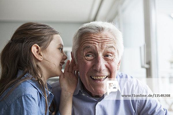 Enkelin  die ihrem Großvater etwas ins Ohr flüstert.