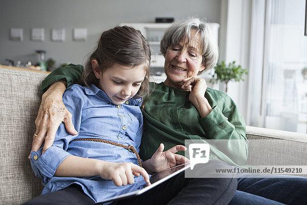 Großmutter und ihre Enkelin sitzen zusammen auf der Couch mit digitalem Tablett