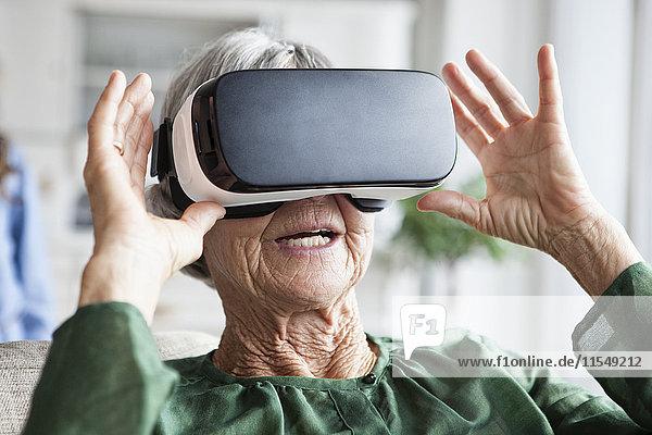 Seniorin mit Virtual Reality Brille zu Hause