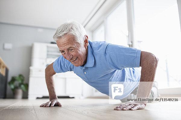 Porträt eines älteren Mannes  der Liegestütze zu Hause macht.